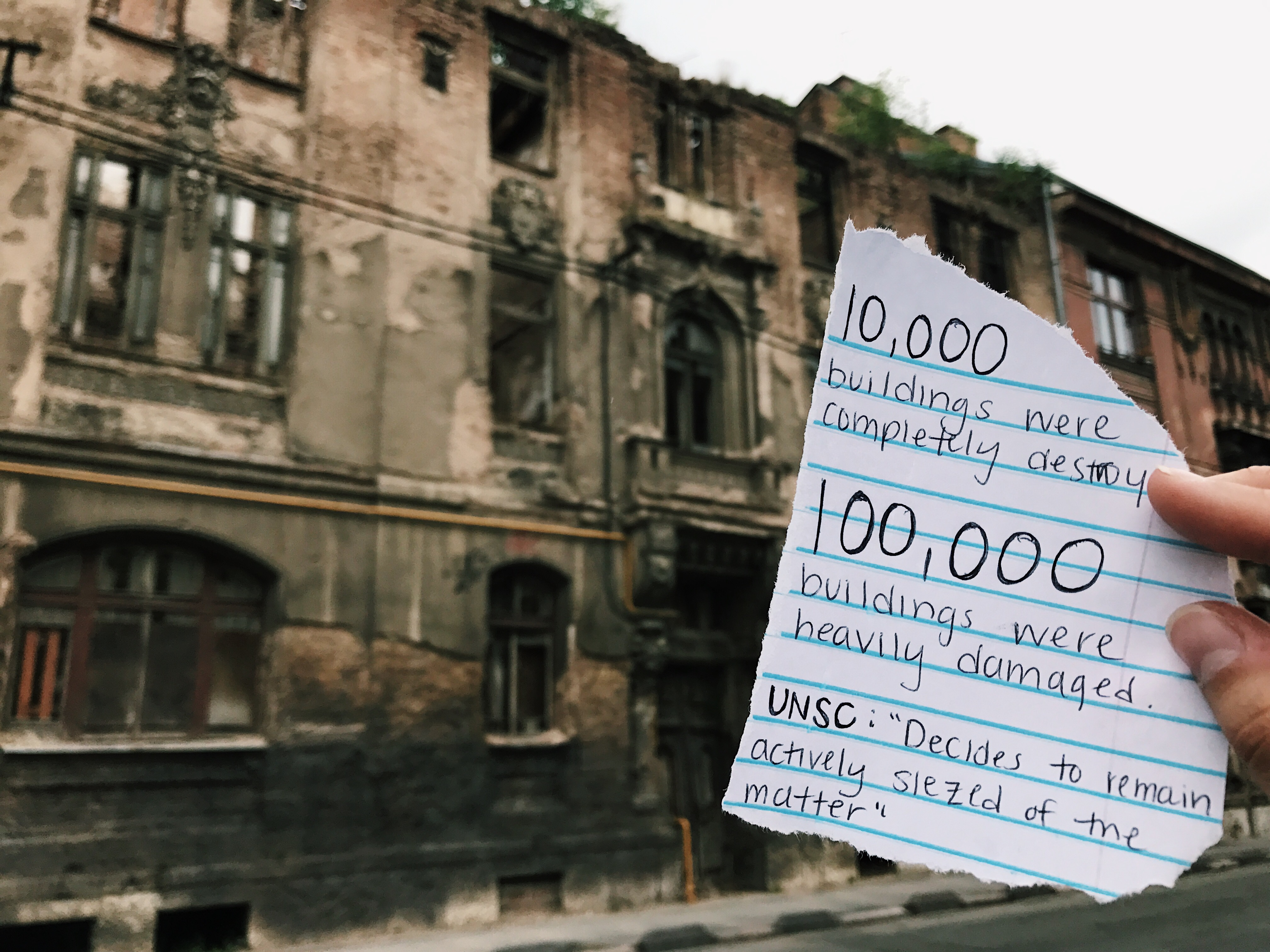 "scrap of paper in front of dilapidated buildings which reads 10,000 buildings were completely destroyed. 100,000 buildings were heavily damaged.  UNSC: ""Decides to remain actively seized of the matter"""
