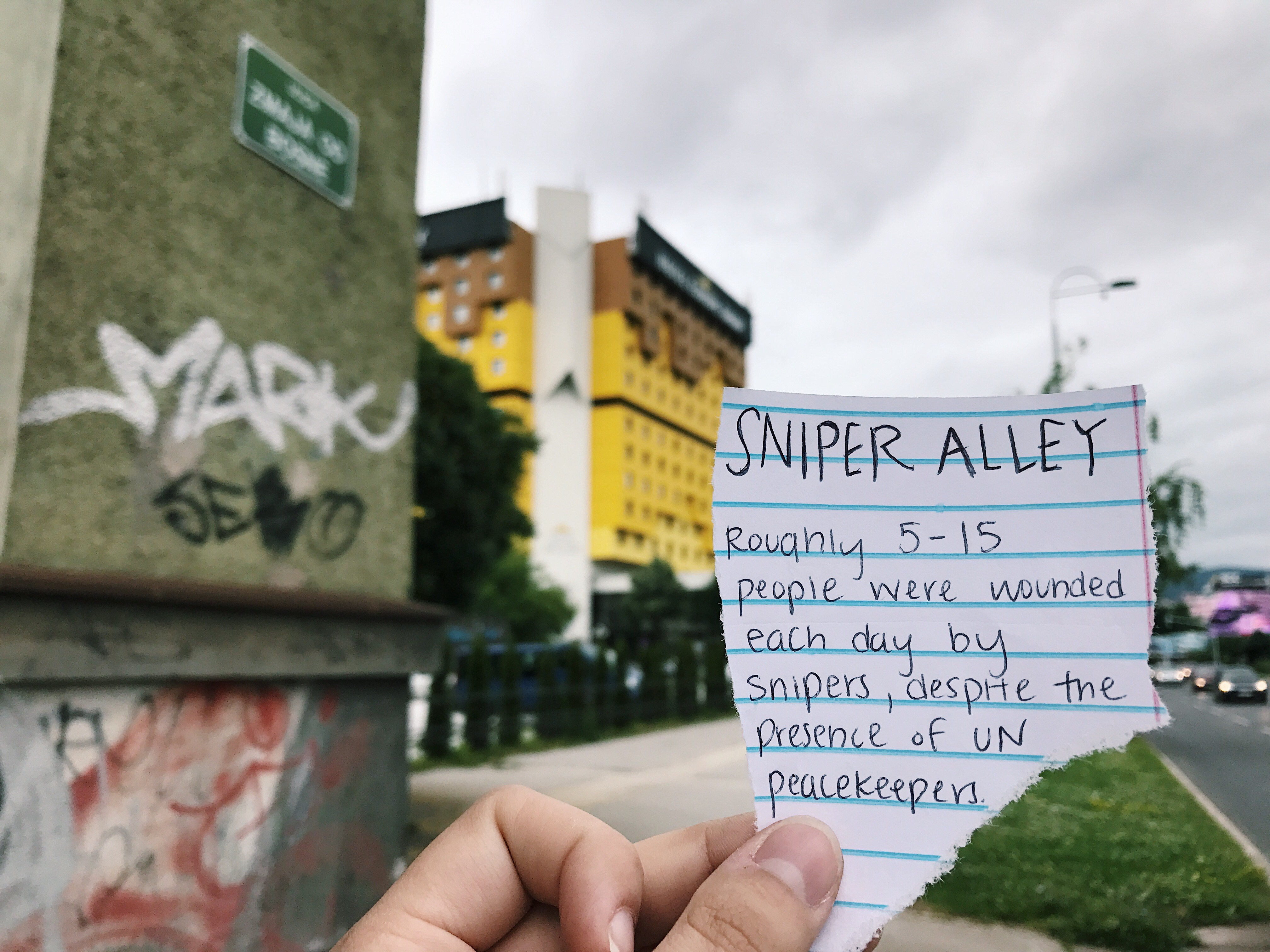 Scrap of paper in front of yellow high rise building which reads, Sniper Alley. Roughly 5-15 people were wounded each day by snipers, despite the presence of UN peacekeepers.