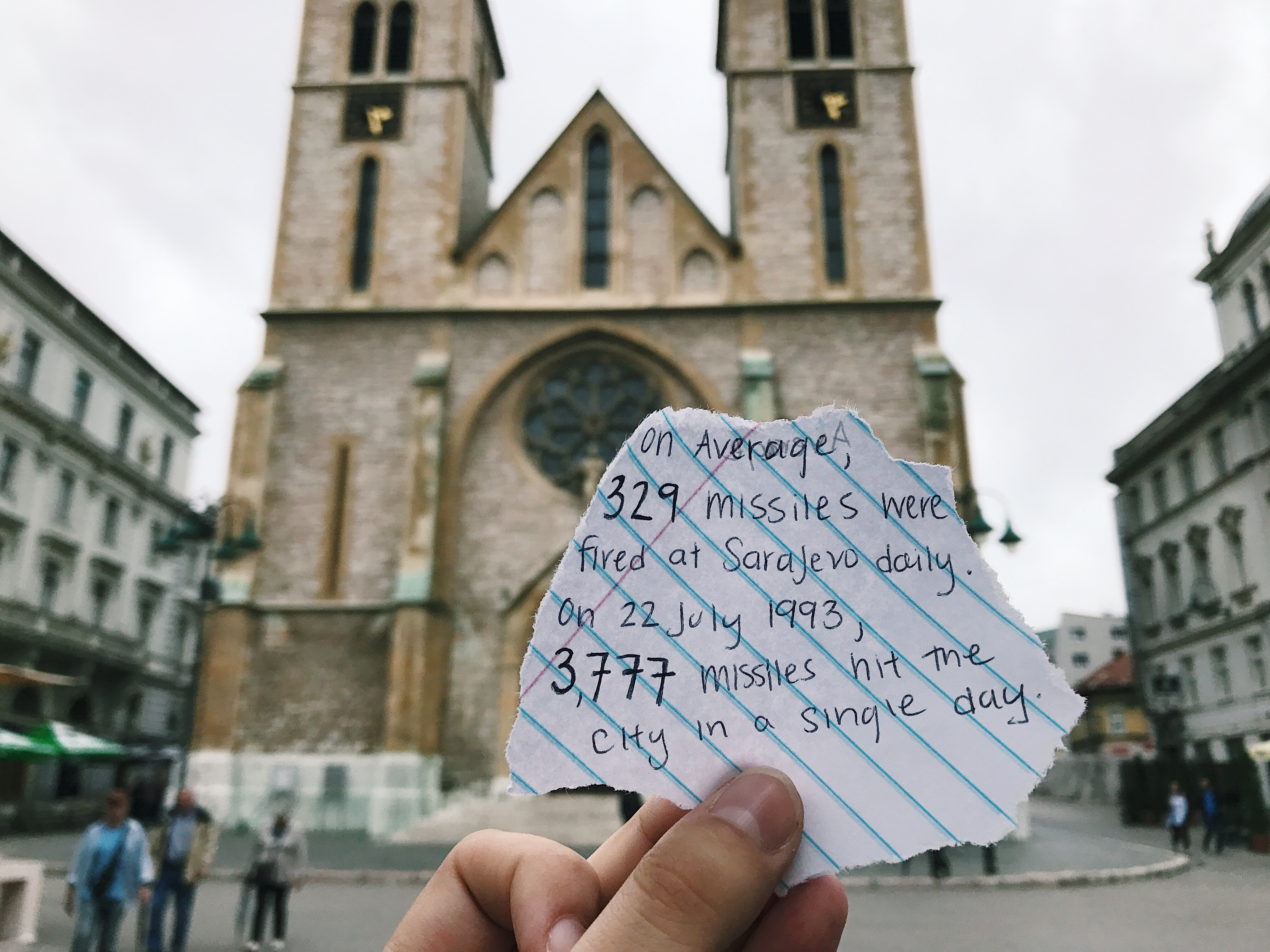 Scrap of paper in front of church which reads on average, 329 missiles were fired at Sarajevo daily. On 22 July 1993,  3,777 missiles hit the city in a single day.